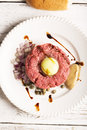 Tartare with egg yolk onions and capers closeup on a white plate Stock Photo