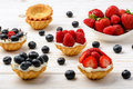 Tartlets with cream, blueberries, raspberries and strawberries on white wooden table. Selective focus. Royalty Free Stock Photo