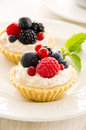 Tartlets with ricotta and fresh fruits as closeup on a white plate Royalty Free Stock Photos