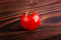 A tasteful red tomato on a brown background. Summer harvest. Natural organic vegetables full of nutrients. Healthy vegan diet.