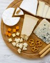 Tasting cheese with bread sticks, walnuts and pretzels on bamboo board over white wooden background, top view. Food for wine. From Royalty Free Stock Photo