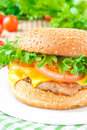 Tasty american lunch cheeseburger with meat cutlet cheese and rissoles cheddar lettuce tomato Stock Image