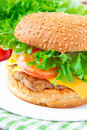 Tasty american lunch cheeseburger with meat cutlet cheese and rissoles cheddar lettuce tomato Stock Photo