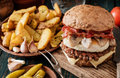 Tasty beefburger with bacon, fried egg and mushrooms and potatoes Royalty Free Stock Photo