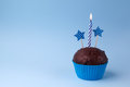 Tasty birthday cupcake with candle, on blue background, with free space Royalty Free Stock Photo