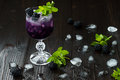Tasty blackberry cocktail in wine glass with mint and ice on dark wooden table. Summer berry lemonade Royalty Free Stock Photo