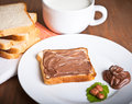 Tasty breakfast bread with chocolate spread and filbert nuts close up Stock Images