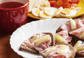 Tasty breakfast bread with ham paprika eggs tomatoes and fruit tea Royalty Free Stock Photography