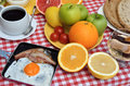 Tasty breakfast or brunch with cup of fresh coffee ham and eggs cereals bread and fruits served on red white tablecloth Stock Photos