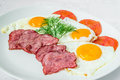 Tasty breakfast. Pieces of bacon, fried eggs and tomatoes with herbs. Horizontal frame Royalty Free Stock Photo