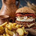 Tasty burger with beef, bacon, fried egg and mushrooms Royalty Free Stock Photo