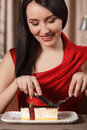 Tasty cake beautiful women in red dress eating cake at the rest woman restaurant Royalty Free Stock Images