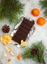 Tasty chocolate bar with mandarins on a snowy background