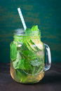 Tasty colourful drink with cold green tea, mint and cucumber in a glass jar on a vintage background