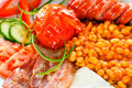 Tasty continental breakfest a closeup of breakfast containing sausages bean truck bacon fresh vegetables fried eggs and bread Royalty Free Stock Photo