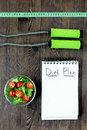 Tasty food for slimming. Notebook for diet plan, salad and fruits on wooden table top view mock up