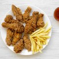 Tasty fried chicken drumsticks, spicy wings, French fries, chicken tenders and sauce on white plate over white wooden surface, top Royalty Free Stock Photo