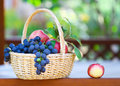 Tasty grapes and apples in the basket in the gazeb gazebo close up Stock Photo
