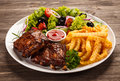 Tasty grilled ribs with vegetables Stock Image