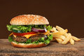 Tasty hamburger and french frites on wood background Royalty Free Stock Image