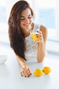 Tasty healthy breakfast. Woman drinking orange juice and smiling Royalty Free Stock Photo