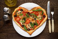 Tasty hot pizza in heart shape with chicken and mushrooms and cutlery on wooden table. Royalty Free Stock Photo