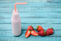 Tasty milkshake in glass bottle with drinking straw and fresh strawberries on wooden table Royalty Free Stock Photo