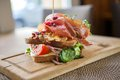 Tasty parma ham sandwich on wooden plate closeup of at cafe Royalty Free Stock Photos