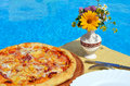 Tasty pizza on the swimming pool background Royalty Free Stock Photo