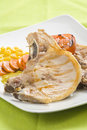 Tasty pork chop with corn carrot tomato Royalty Free Stock Photo