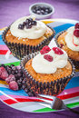 Tasty raspberry and blueberries muffin on the color plate Royalty Free Stock Image