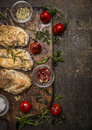 Tasty roasted chicken fillet with herbs,spices,seasoning and tomatoes on vintage gutting board over rustic wooden background, top Royalty Free Stock Photo