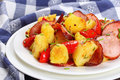Tasty roasted potato wedges with sausages