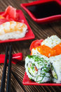 Tasty rolls served on red plate with chopsticks wooden table Royalty Free Stock Photos
