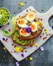 Tasty sandwich with avocado boiled eggs, pumpkin seed and edible viola flowers in a white board. healthy food Royalty Free Stock Photo