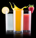 Tasty summer fruit drinks in glass with splash isolated on a black background Royalty Free Stock Photos