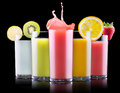 Tasty summer fruit drinks in glass with splash isolated on a black background Stock Images