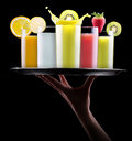 Tasty summer fruit drinks in glass with splash isolated on a black background Stock Image