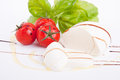 Tasty tomatoe mozzarella salad with basil on white Royalty Free Stock Photo