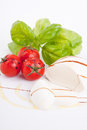 Tasty tomatoe mozzarella salad with basil on white Stock Image