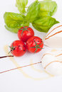 Tasty tomatoe mozzarella salad with basil on white Royalty Free Stock Photography
