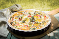 Tasty vegetarian quiche on a summer picnic table outdoors with eggplant eggs cheese tomato and herbs for healthy lunchtime party Stock Photo