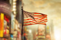 Tattered american flag blowing in the wind against cool city blurred background Stock Photos