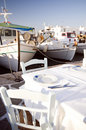 Taverna setting in harbor with fishing boats Royalty Free Stock Photo