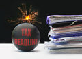 Tax deadline exploding bomb labeled next to a pile of paperwork Stock Image