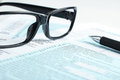 Tax form financial concept business with a pair of black glasses and a pen aside Stock Photos