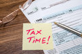 Tax time word on tax form with calculator, pen Royalty Free Stock Photo