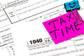 Tax time written on a bright sticker note paper clip for a tax Royalty Free Stock Photo