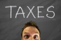 Taxes mans head with a message on a blackboard Stock Image