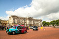 Taxi at buckingham palace london united kingdom july a is driving by the followed by few cars tourists are waiting for the change Royalty Free Stock Photography